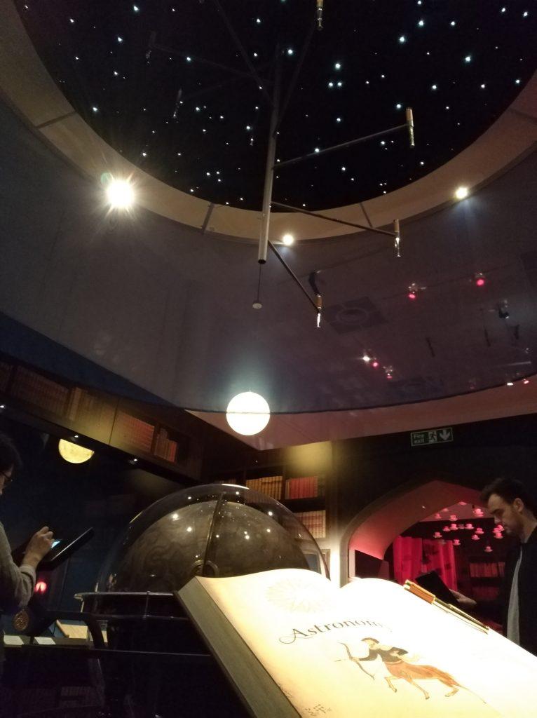 Section astronomie de l'expositon Harry de la British Library avec un globe et un système solaire au plafond