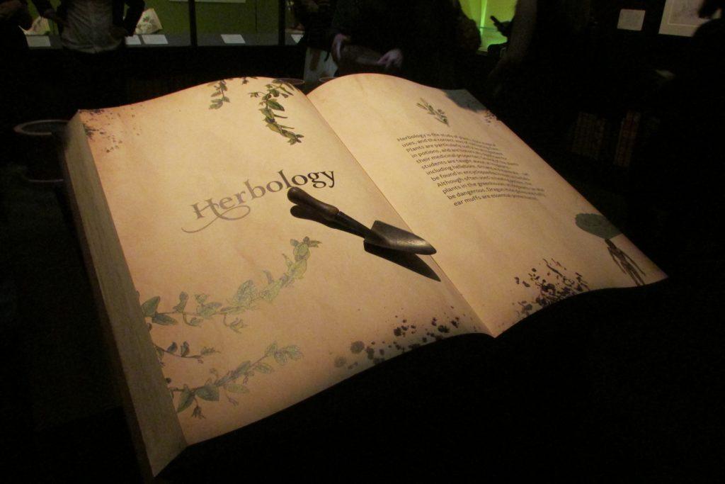 Livre ouvert introduisant la section botanique de l'exposition Harry Potter de la British Library avec une petite pelle de jardinage dessus