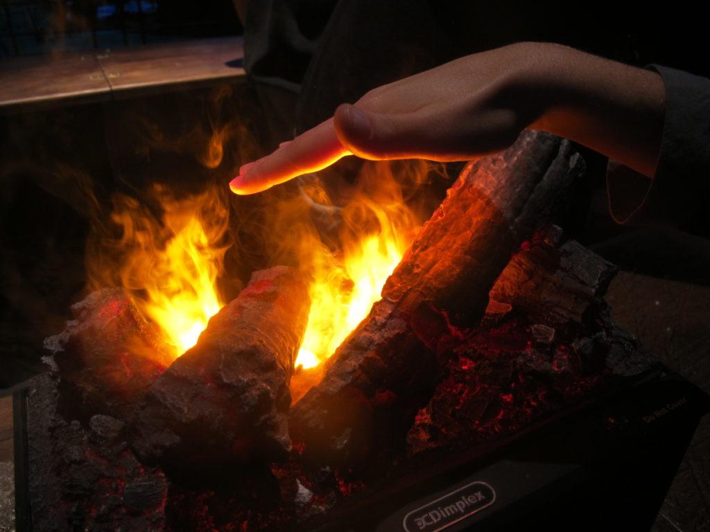 Main au dessus des flammes d'un faux feu de cheminée de Poudlard lors de Hogwarts in the snow au au Warner Bros. Studio Tour London: The Making of Harry Potter