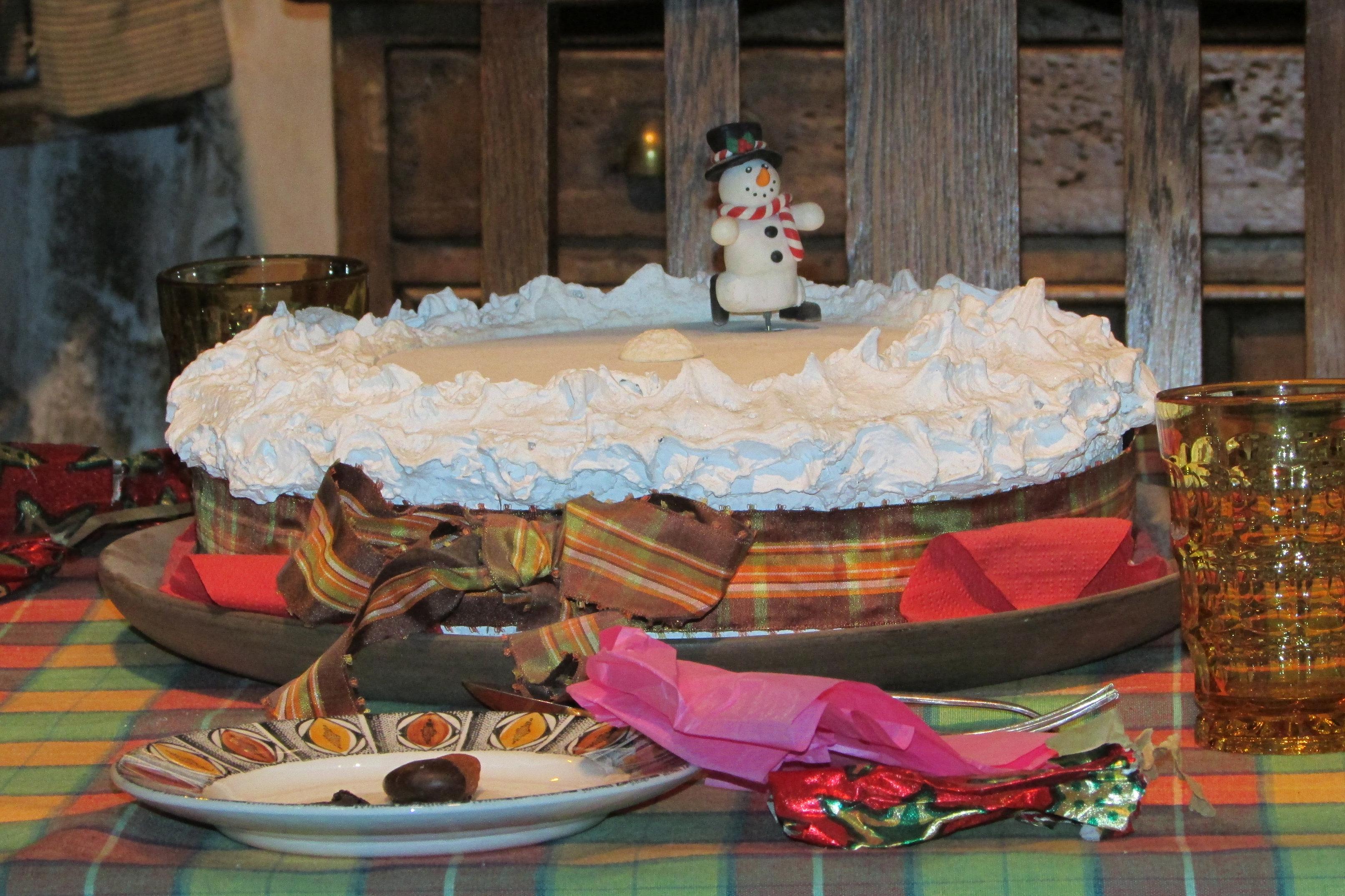 Un gâteau sur la table du Terrier, couvert de glaçage et d'un bonhomme de neige qui danse lors de Hogwarts in the snow au Warner Bros. Studio Tour London: The Making of Harry Potter