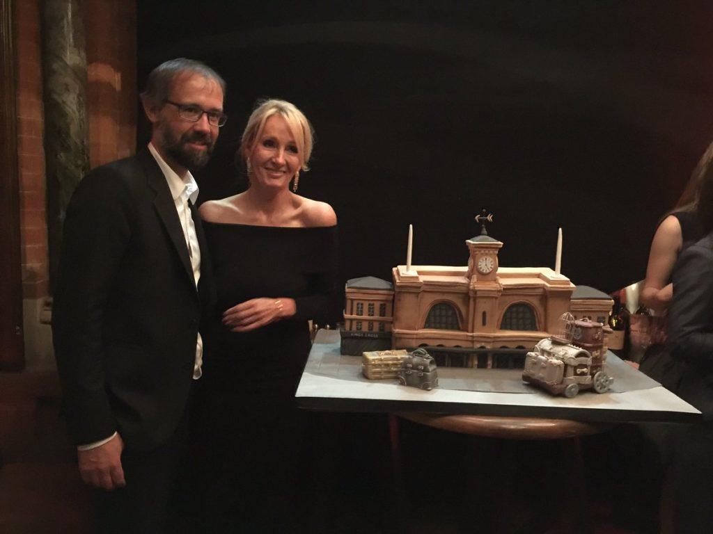 JK Rowling et son mari à côté du gâteau King's Cross célébrant la première représentation de Harry Potter & the Cursed Child à Londres