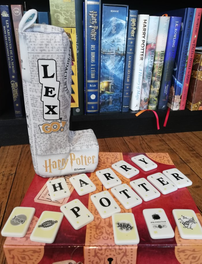 Pochette de Lex Go Harry Potter posée sur un coffret de la saga. Harry Potter écrit en tuiles du jeu, sur fond de bibliothèque.