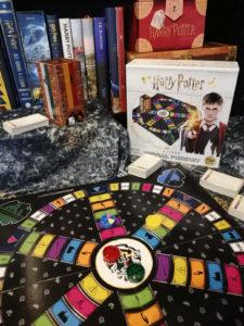 Photo du plateau de Trivial Pursuit Harry Potter, avec boîte de jeu, sur fond de bibliothèque