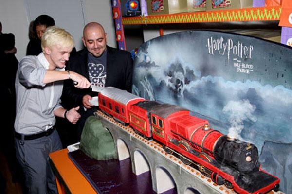 Tom Felton découpe un gâteau en forme de Poudlard Express lors de l'avant-première de Harry Potter et le Prince de Sang-mêlé à New York