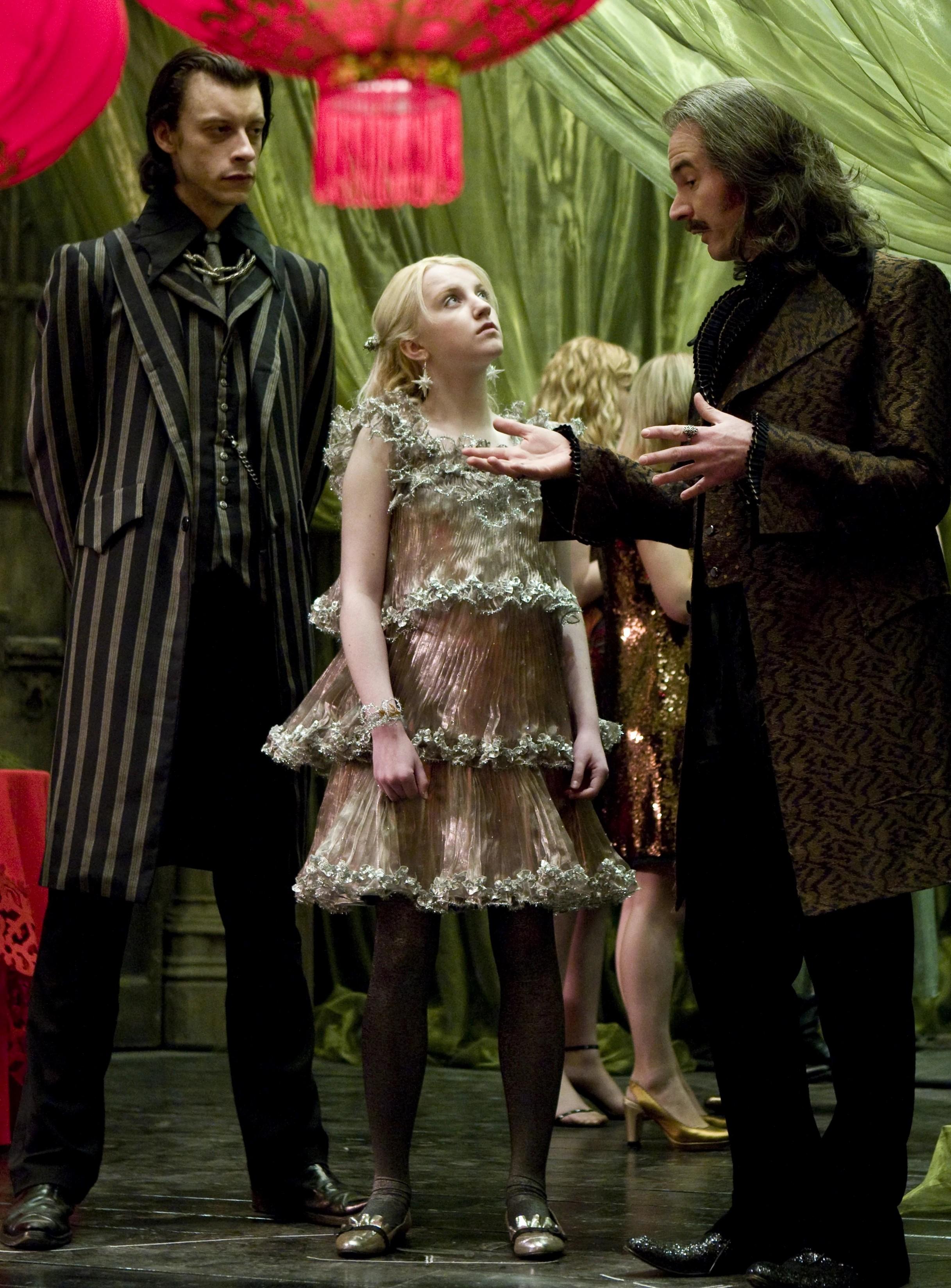 Soirée de Noël de Slughorn. Eldred Worped parle à Luna, que Sanguini observe.