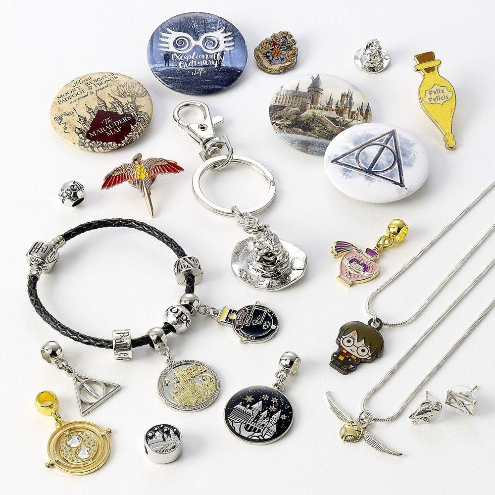 Détail du contenu du calendrier 2021 de The Carat Shop : badges, pins, pendentifs, charms pour bracelets et breloques thématisés retourneur de temps, reliques de la mort, vif dor et autres objets et personnages en style chibi.